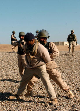 Police officers from the 3rd Public Order Battalion train on detaining prisoners at a makeshift check point at Forward                                     Operating Base Seven in December. The officers were to begin policing the city of Samarra at the end of the month. They were                                     being trained by military and civilian officials, include George Clark, an international police officer and Philadelphia resident                                     who played the role of the detainee. (Photo by Spc. Ismail Turay Jr., 196th MPAD)